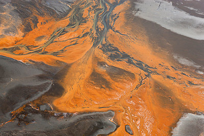 Aerial view of river estuary or delta, coloured orange by sewerage outlet. - p1100m1520296 by Mint Images