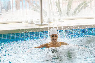 Young woman with swimming cap relaxing under a waterfall jet in a spa - p1166m2189697 by Cavan Images