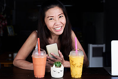 Portrait of happy woman with cell phone and smoothies - p300m1535447 by Ivan Gener Garcia