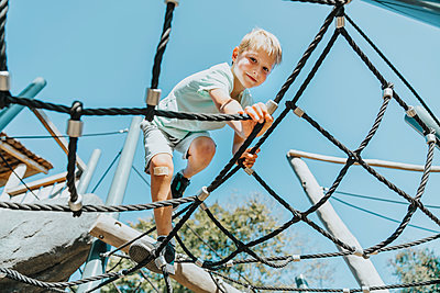 Boy climbing on spider web in public park during sunny day - p300m2226861 by Mareen Fischinger