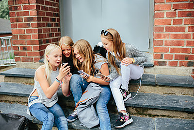 Girls sitting on steps and using cell phone - p312m1471028 by Anna Rostrom