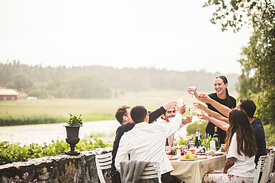 Cheerful male and female friends toasting wineglasses during dinner party in backyard - p426m2035690 by Maskot