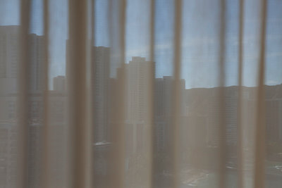 View of Waikiki Beach through a curtain window - p495m1034285 by Jeanene Scott