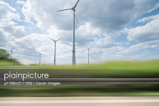 Blurred motion of plants against windmills - p1166m2111932 by Cavan Images