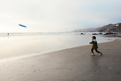 Boy throwing Frisbee while standing on shore at beach against sky - p1166m1509695 by Cavan Images