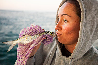 Young woman pretending to kiss caught fish, Perth, Western Australia, Australia - p1166m2202093 by Christopher Kimmel / Alpine Edge Photography