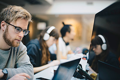 Male programmer working on computer with colleagues at desk in office - p426m1493982 by Maskot