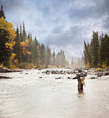 Caucasian man fishing in river - p555m1301795 by Mike Kemp