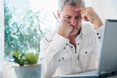 Frustrated older Caucasian man using laptop - p555m1304921 by JGI/Jamie Grill