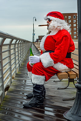 Man dressed in Santa suit, sitting on bench, smoking cigar, holding bottle of beer - p924m1422832 by Sue Barr