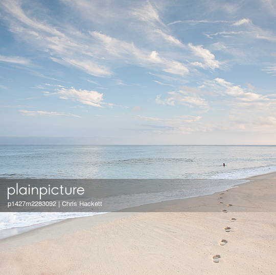 USA, Massachusetts, Cape Cod, Nantucket Island, Footprints on beach and woman swimming in ocean in distance - p1427m2283092 by Chris Hackett