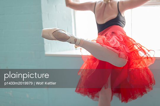 A mature ballet dancer practises her attitude derriere by the window. - p1433m2019979 by Wolf Kettler