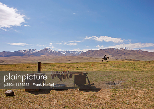 Fleisch beim Räuchern mit Reiter im Hintergrund - p390m1159283 von Frank Herfort