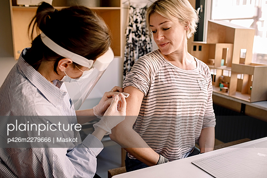 Female nurse injecting medicine to blond woman at home - p426m2279666 by Maskot