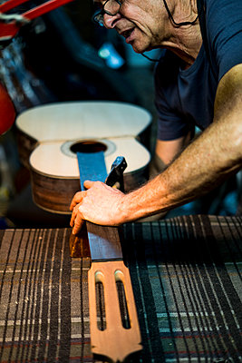 Luthier man making guitars in artisan workshop in Spain. - p1166m2129680 by Cavan Images
