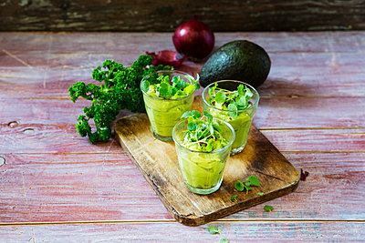 Glasses of avocado cream with chili flakes, cress and parsley - p300m1568180 von Kai Schwabe