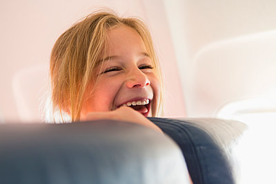 Caucasian girl laughing on airplane - p555m1453380 by Marc Romanelli