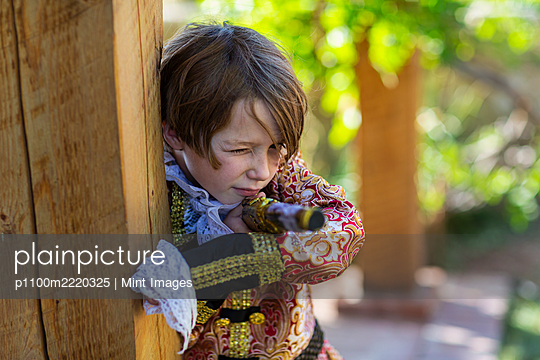 Young boy dressed as a pirate holding long pistol. - p1100m2220325 by Mint Images