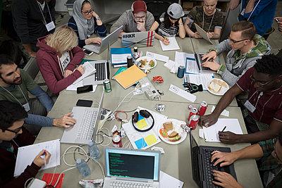 Hackers working hackathon at laptops in workshop - p1192m1202032 by Hero Images