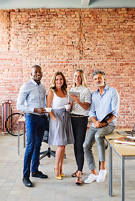Portrait of smiling colleagues at desk in loft office - p300m1535384 by HalfPoint