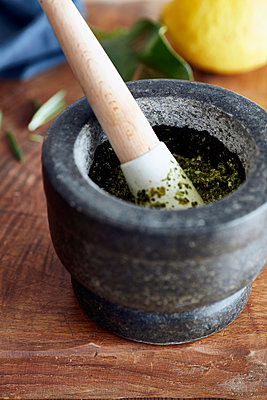 Close up of pestle and mortar with pesto on cutting board - p429m1417742 by Debby Lewis-Harrison