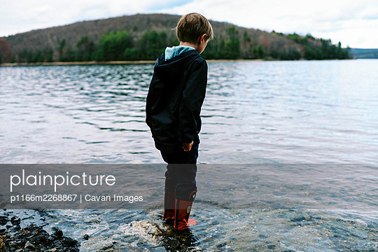 Little boy in red rubber boots walking through blue pristine water - p1166m2268867 by Cavan Images