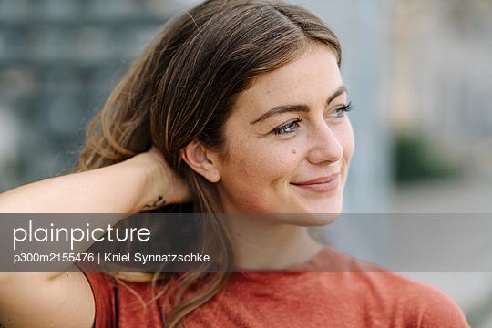 Portrait of smiling young brunette woman, looking sideways - p300m2155476 by Kniel Synnatzschke