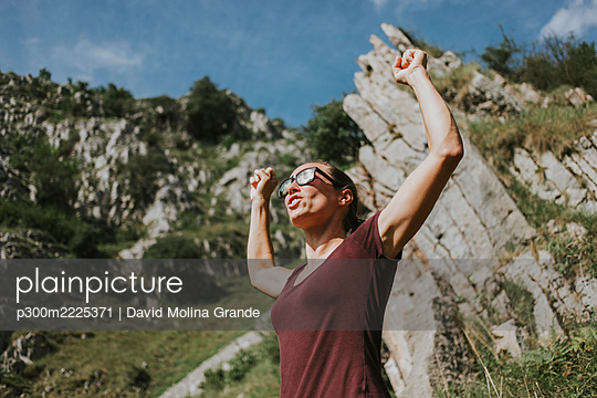 Woman celebrating victory with arms raised against mountain on sunny day - p300m2225371 by David Molina Grande