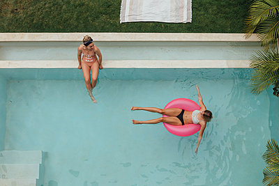 Two young women relaxing in swimming pool - p300m2103465 von letizia haessig photography