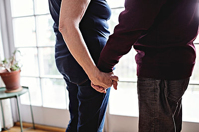 Midsection of retired couple holding hands standing by window at home - p426m1569848 by Maskot