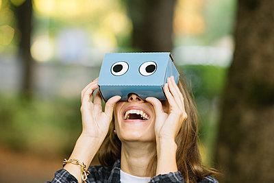 Young woman looking up through cardboard binoculars in park - p429m1504947 by Alberto Bogo