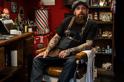 Hairdresser sitting on chair in salon - p623m2214747 by Frederic Cirou