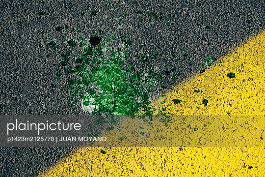 Green glass bits on the asphalt - p1423m2125770 by JUAN MOYANO