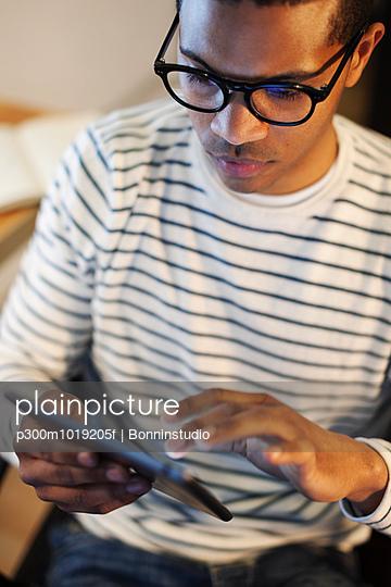 Young creative man using mini tablet - p300m1019205f by Bonninstudio