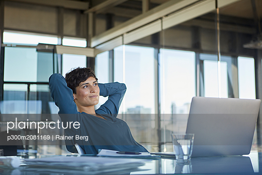 Smiling businesswoman sitting at desk in office with laptop having a break - p300m2081169 by Rainer Berg