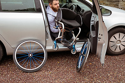 Disabled young man holding wheelchair while boarding in his car - p1315m1566290 by Wavebreak