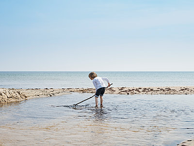 Boy playing in shallow water, Baltic Sea, Sweden - p1481m2203867 by Peo Olsson