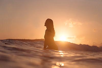 Indonesia, Lombok, female surfer sitting on surfboard at sunset - p300m1568157 by Konstantin Trubavin