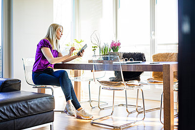 Woman sitting at table at home using tablet - p300m1587135 by Robijn Page