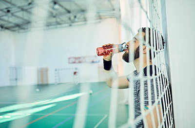 Basketball player drinking from plastic bottle - p300m1588125 by Zeljko Dangubic