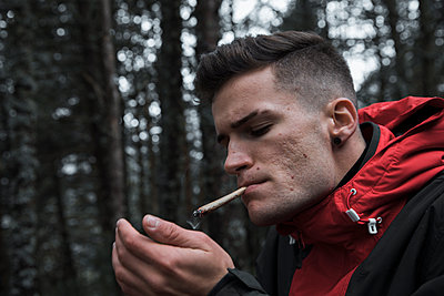 Man smoking cigarette while standing in forest during autumn - p300m2224869 by Aitor Carrera Porté