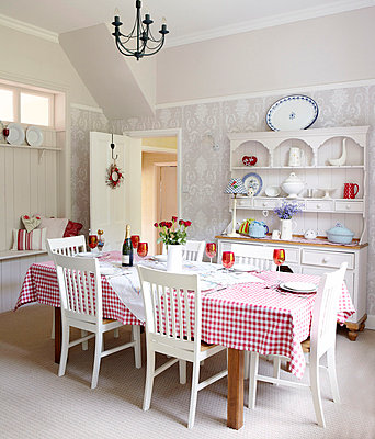 Checked tablecloth with grey patterned wallpaper in dining room family home - p349m790162 by Brent Darby