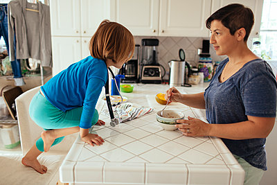 Caucasian mother and daughter having breakfast in kitchen - p555m1409610 by Shestock