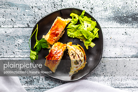 Swiss roll, puff pastry with sausage meat, cheese, onion, parsley and salad on plate - p300m2023665 von Sandra Roesch