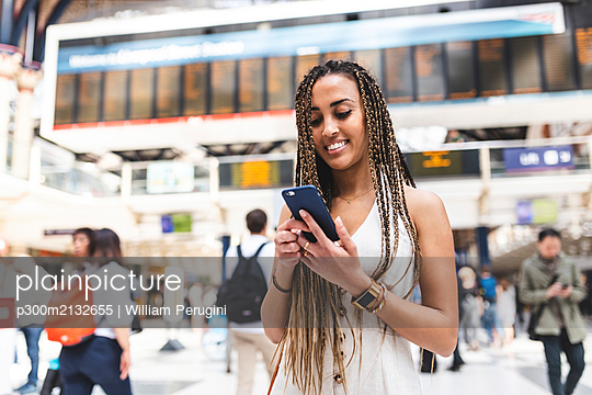 Portrait of happy young woman at train station using smartphone, London, UK - p300m2132655 by William Perugini
