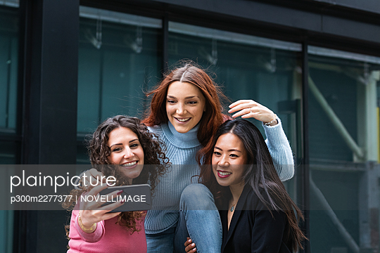 Smiling woman taking selfie through mobile phone with friends - p300m2277377 by NOVELLIMAGE