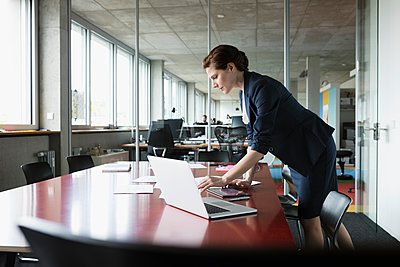 Businesswoman working at laptop in conference room - p1192m1493272 by Hero Images