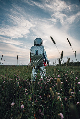 Spaceman exploring nature, standing in meadow, looking at sky - p300m2030547 by Vasily Pindyurin