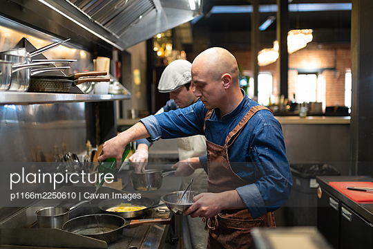 Male cooks working in cafeteria - p1166m2250610 by Cavan Images