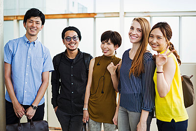 Small group of people standing on the platform of a subway station, Tokyo commuters.  - p1100m1531105 by Mint Images